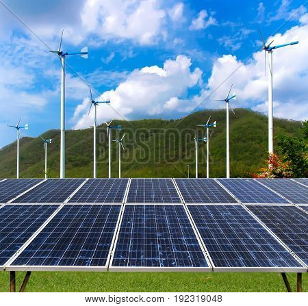 Eco power. Solar panel and wind turbines generating electricity clean energy on green grass with mountain and cloud on blue sky background