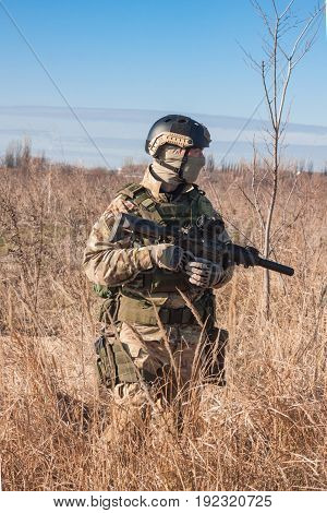 airsoft soldier in fields posing with combat rifle