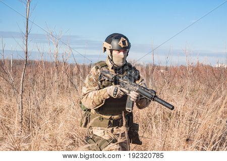 aiming, airsoft player with gun, helmet and bulletproof vest walking in fields