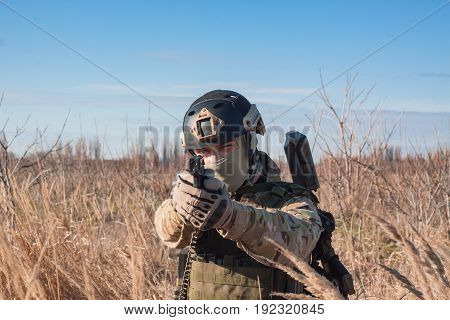 Close up picture of airsoft soldier with a combat pistol in fields