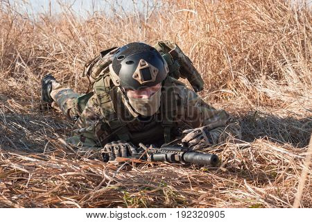 crawling airsoft soldier with a rifle, fields background