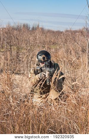 airsoft soldier with a rifle and full amunition sitting in bushes