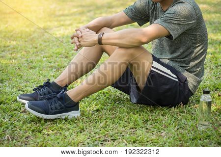 Healthy male athlete is resting on grass and bottle of water.