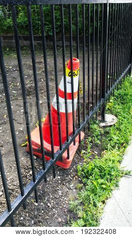 Orange construction cone with white stripes behind a black metal fence.