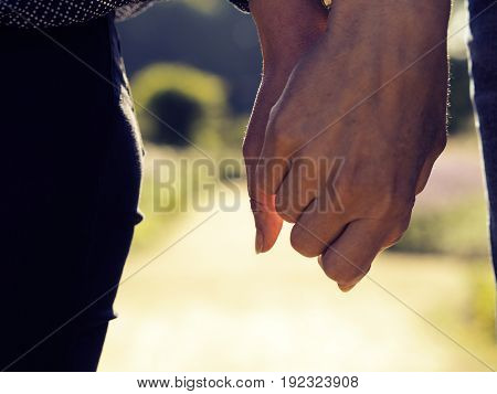 Couple holding hands in a park close up shot warm color toned
