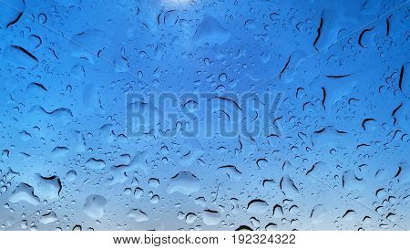 Blue colored rain drops on a windshield after a rain storm