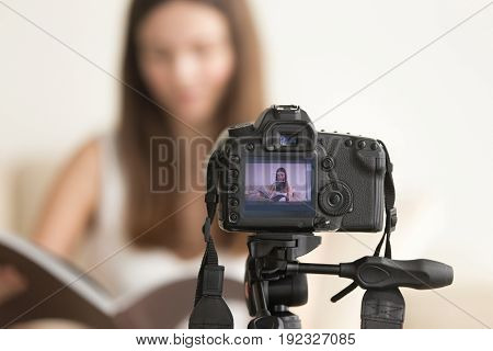 Close up photo of camera on tripod with young woman reading book image on LCD back screen and blurred scene on background. Female video blogger recording vlog or podcast, streaming online from home
