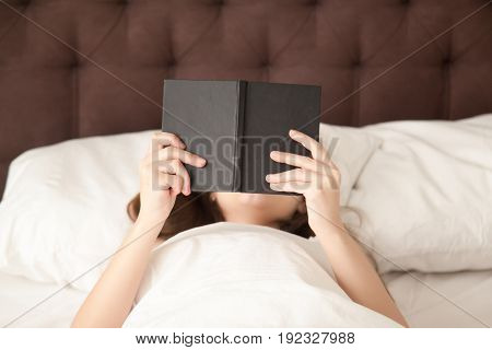 Close up photo of woman reading paper book with black binding before going to sleep. Lady relaxing in cozy bed with favorite book in hands, enjoying good literature, checking plans on day in work note