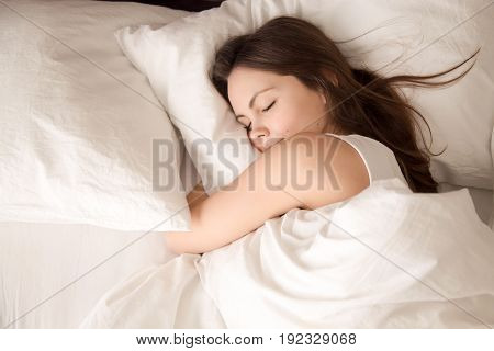 Top view of young woman sleeping well in bed hugging soft white pillow. Teenage girl resting, good night sleep concept. Lady enjoys fresh soft bedding linen and mattress in bedroom