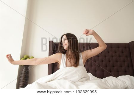 Happy cute woman stretching in bed, looking in window with smile after morning wake up. Young positive lady gets ready for new start, full of strength, expectations of new pleasures on vacation Sunday