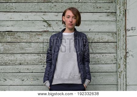portrait of beautiful young angry woman in white t-shirt on wooden background
