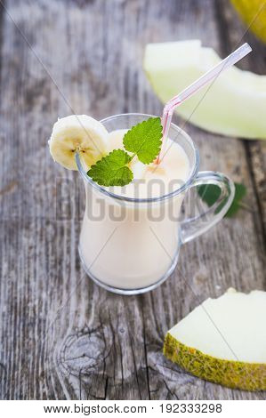 Yogurt and smoothie with melon on a wooden table. Different tasty dairy products with melon. Healthy eating.