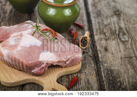 Raw pork on a wooden cutting board. Pork and pots on the table. Cooking.