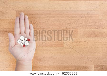 hand holding heap of capsule pill on wooden background
