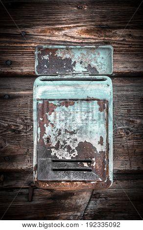 Rusty metal mailbox on the wooden doorway