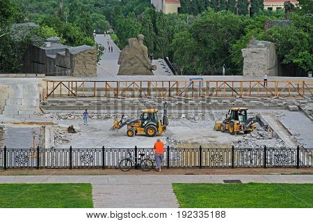 Volgograd Russia - June 24 2014: Cyclist watching the repair works of the bottom of the