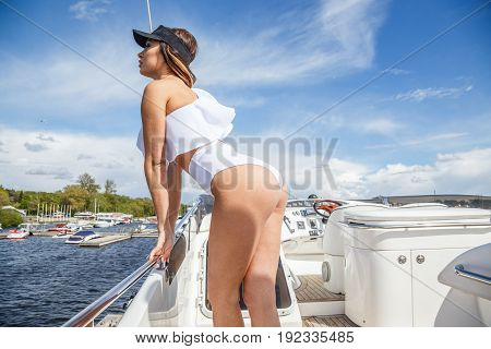 Beautiful blond woman in swimsuit posing at the port near the yacht, on the yacht