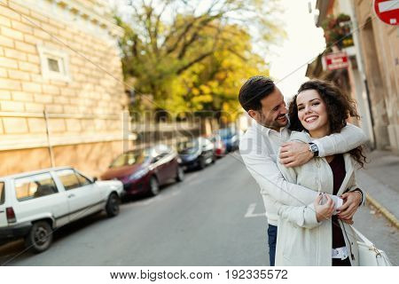 Happy young couple in love spending time together on street