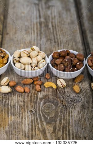 White Bowls With Nuts On A  Wooden Table