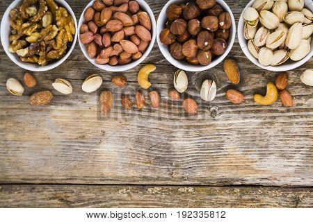 Four Bowls With Nuts On A  Wooden Table