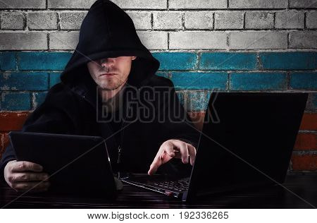 A Hacker Sitting At A Desk With A Computer And A Tablet In His Hand