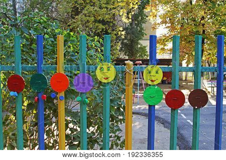 Homemade children's art object in the form of a caterpillar on a fence of multi-colored circles wire and bottle caps