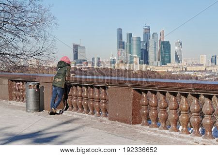 Moscow Russia - February 17 2015: Woman stands on observation deck of the Vorobyovy Gory and watching to the business center
