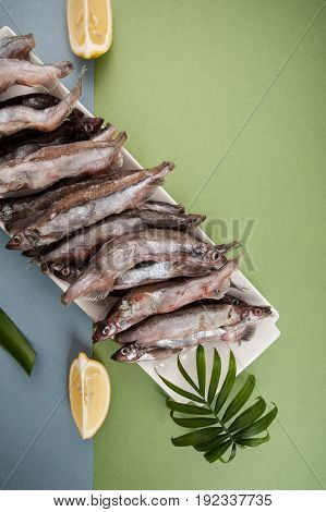 Minimalistic Composition With Freshly Frozen Capelin And Lemon On A Blue-green Background.