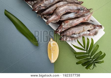 Raw Fresh-frozen Capelin, Served With Lemon On A Light Blue-green Background..