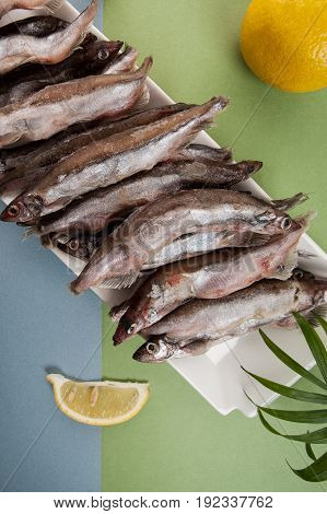 Freshly Frozen Capelin Lies On A White Plate On A Light Blue-green Background..