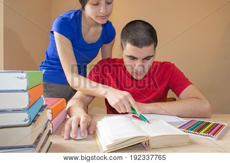 Older brother and Student sister reading Books At Desk In Living Room education concept