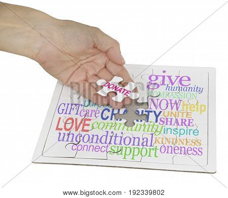 Donate to Charity Puzzle  - hand holding a jigsaw puzzle piece showing the word DONATE, the remainder of the puzzle contains a charity word cloud on white background