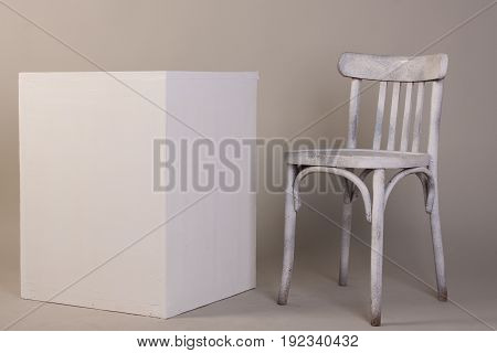 Old White Wooden Chair And Cube Isolated On A Gray Background