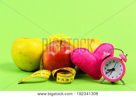 Apples with rolled yellow measuring tape with pink toy heart and vintage alarm clock isolated on green background copy space. Concept of fruit diet time and valentines day