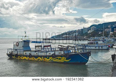 Pier for small ships on Yalta (Crimea Ukraine) sea front at autumnal evening.