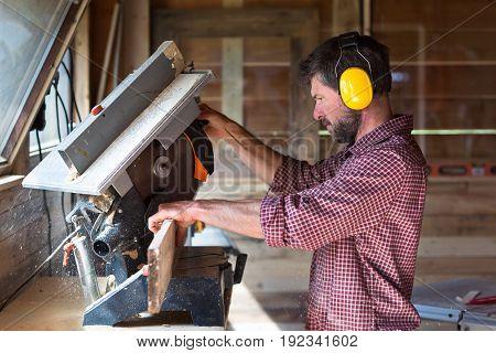 Male Carpenter Cutting Plank By Circular Saw