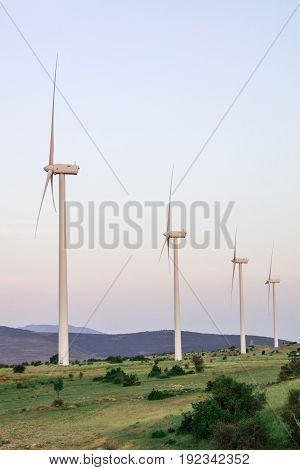 A photo of wind turbines in Castilla la Mancha, Spain, in the sunset