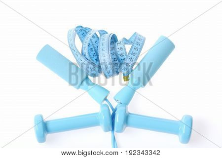 Blue measuring tape making art composition with skipping rope handles and cyan dumbbells isolated on white background top view. Concept of slim shape and sports