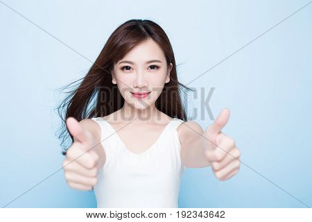 beauty woman show thumbup on the blue background