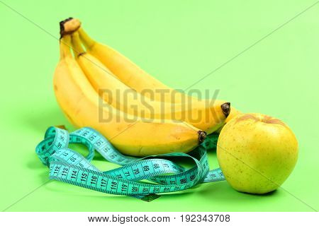 Bunch Of Bananas Near Ripe Apple And Tape For Measuring