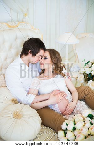 Beautiful couple, pregnant young woman and man, hugging lovingly sitting on the bed, in a home interior