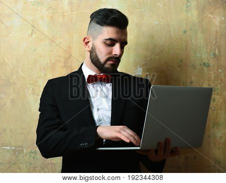 Finance or project manager with attentive and serious face expression modern hairstyle and classic outfit holds laptop on painted background. Concept of business and work