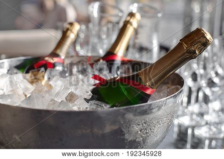 Three wine bottles chill in ice bucket on a buffet table among glasses