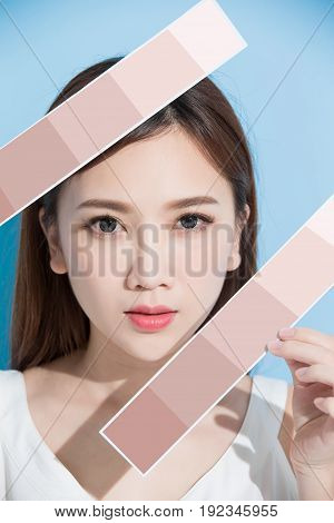 woman take skin color scale on the blue background