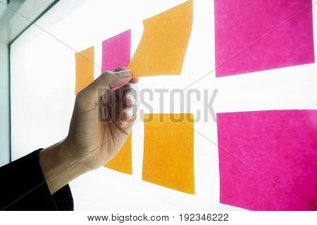 Note paper reminder schedule board. Business people meeting and use post it notes to share idea. Discussing - business teamwork brainstorming concept.