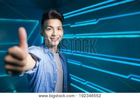 man smile happily and thumb up on the technology background