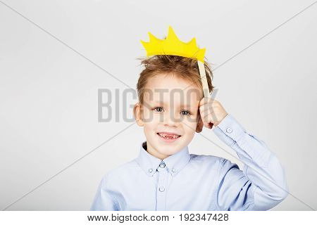 Portrait Of A Cute Little School Boy With Yellow Paper Crown Against A White Background. Cheerful Sm