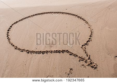 A speech or think bubble drawn out on a sandy beach. Beach background. Top view