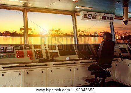 wheelhouse control board of modern industry ship approaching to harbor at night