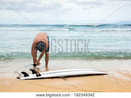 Surfer Stands On Sand Near Ocean